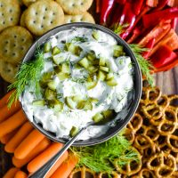 pickle dip in bowl surrounded by crackers and veggies