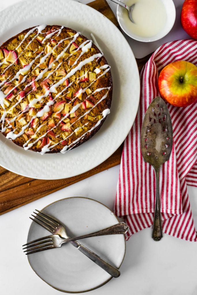apple cake on platter with serving utensils beside