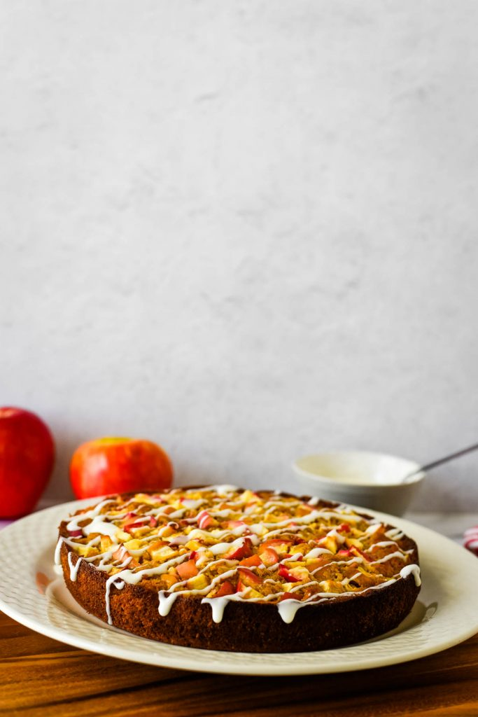 sourdough apple cake on platter with apples behind