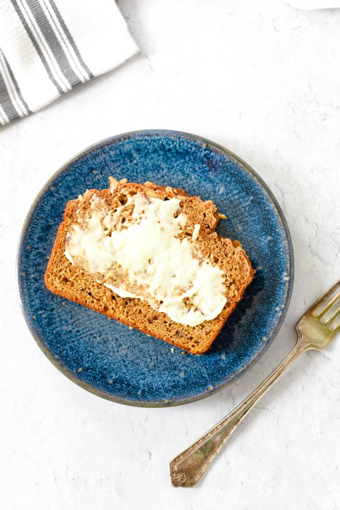 slice of pumpkin bread on blue plate with butter and fork
