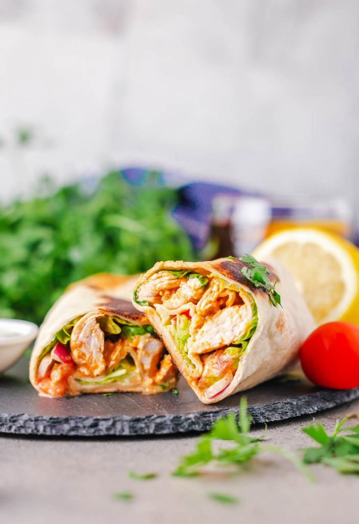 two chicken wraps with buffalo sauce and veggies