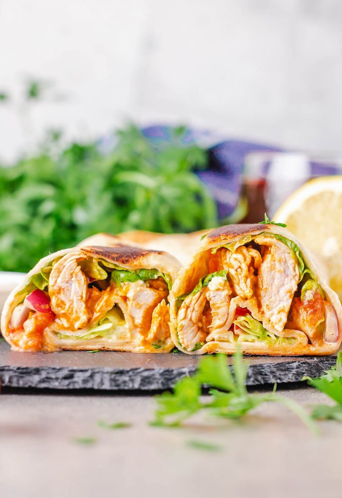 buffalo chicken wraps on plate with lettuce behind
