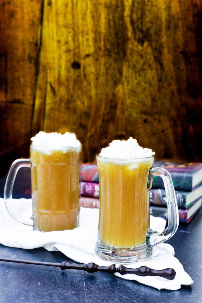 two mugs of butterbeer next to wand