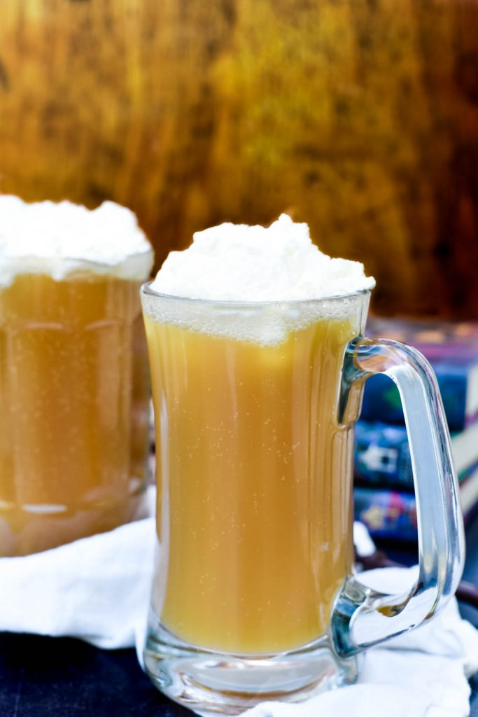 two mugs of butterbeer in front of stack of books