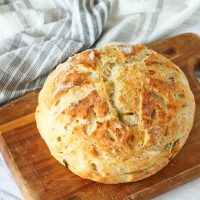 round sourdough bread on cutting board with kitchen towel