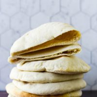 stack of sourdough pita with top one cut open